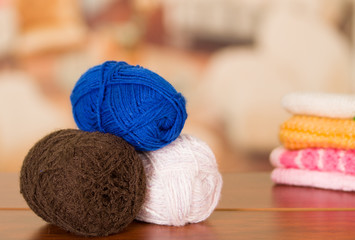 Brown, white and blue yarn balls stacked on table desk, blurry background