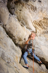 Male lead climber is climbing big boulder in nature. Man is holding climbing rope by his mouth and searching for the next grip. Summer time. Climbing equipment