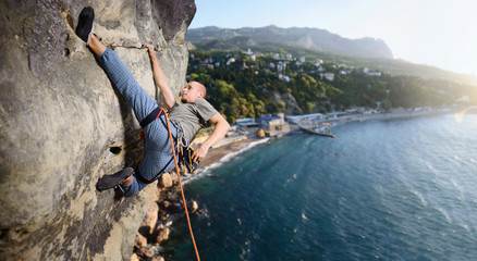 Portrait of young athletic male climber making difficult move up on overhanging cliff against scenic sea coast background. Climbing equipment. Summer time. Panoramic picture