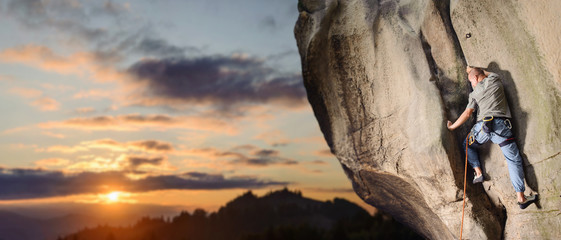 Strong male rock climber climbing challenging route on rock wall with rope against scenic sunset background. Summer time. Climbing equipment. Panorama