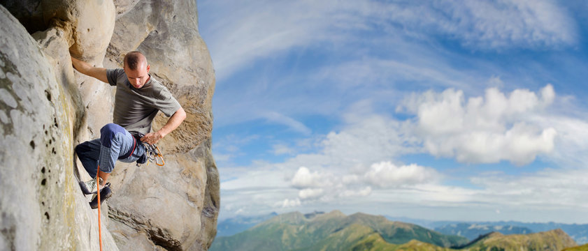 Strong male rock climber climbs with rope and carbines on multi-pitch against blue sky and scenic mountain background. Climber is hanging on one hand and searching for carabine. Summertime. Panorama