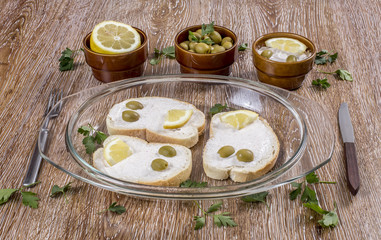 Breakfast with taramasalata canape, lemon and green olives on wooden background