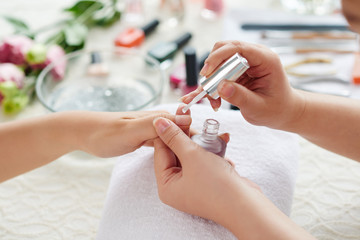 Manicurist applying transparent base coat to nail