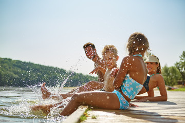 Familie am See hält Füße ins Wasser