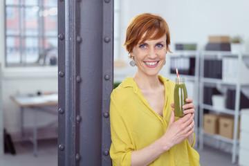 frau im büro trinkt einen gesunden grünen smoothie