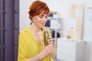 frau trinkt grünen smoothie in der pause im büro