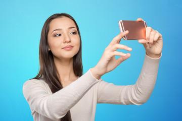 Joyful young women making selfie by her smart phone