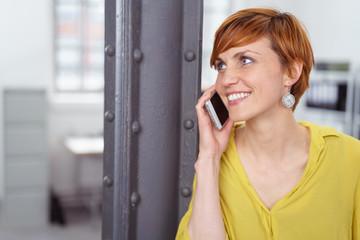 frau telefoniert im büro mit ihrem handy