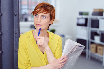 geschäftsfrau steht im büro mit der tageszeitung und schaut nachdenklich zur seite