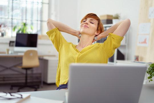 frau im büro lehnt sich entspannt zurück