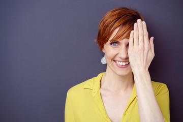 lächelnde frau hält eine hand vor ihr gesicht