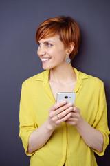 frau hält ihr smartphone in der hand und schaut lächelnd zur seite