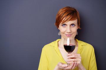 frau hält ein glas rotwein in der hand