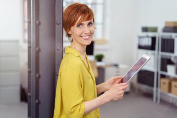 lächelnde mitarbeiterin im büro mit tablet