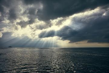 dramatic sky with sun rays over the sea