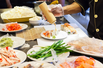 Preparing of sushi rolls with salmon