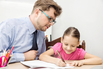 teacher and schoolgirl, father and daughter writing in classroom