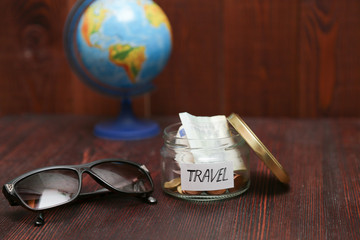 Jar with savings for travel, brown sunglasses, globe at background