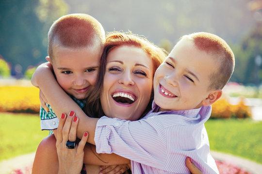 happy mother sons hug park summer