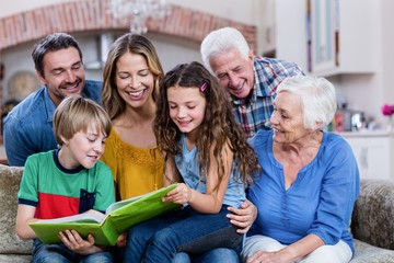 Multi-generation family looking at a photo album