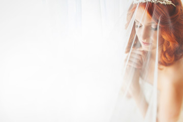 Redhead bride is covered by the bridal veil