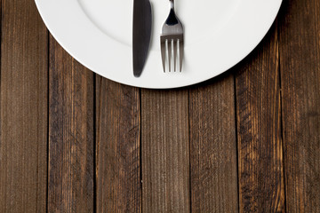 Fork and knife with white plate on dark wooden background, empty space on bottom