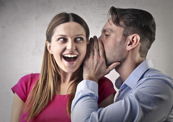 Man whispering a secret to his girlfriend