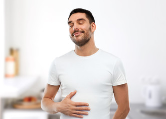 happy full man touching tummy over kitchen