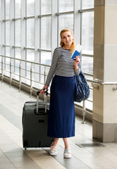 A tourist blonde woman in a striped sweater with a suitcase and passport and tickets at the station or terminal.