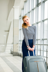 A tourist blonde woman in a striped jacket comes with a suitcase at the railway station or terminal. Girl pulls luggage