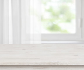 Wooden table surface on defocused half curtained window background