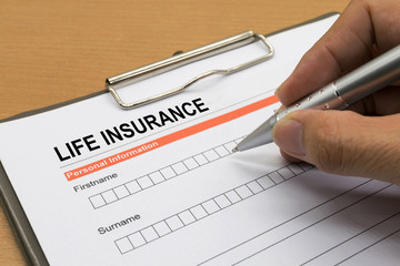 man signing a life insurance policy