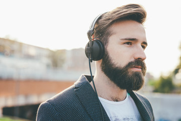 Portrait of young handsome bearded man listening music with earphones, overlooking - music, relaxing, technology concept