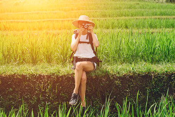 Traveler with photo camera sitting among rice terraces (intentional sun glare)