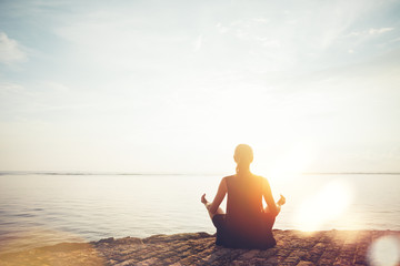 Young woman doing meditation practice on the beach. Intentional sun glare and lens flare effect Wall mural