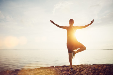 Fotomurais - Young woman standing in yoga pose on the beach and meeting sunrise. Intentional sun glare, lens flare effect