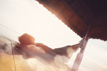 Fotomurais - Pretty woman resting under sun shelter on the beach. Blurred effect, lens flares effect, intentional sun glare