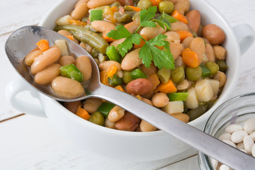 White beans with vegetables on white wooden table