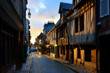 Fototapete - Picturesque street in the Normandy town of Honfleur, France with light of the rising sun