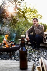 Mature man sitting by fire pit with beer, relaxing