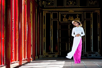 Mid adult woman wearing ao dai dress and conical hat standing in imperial palace looking away, Hue, Vietnam