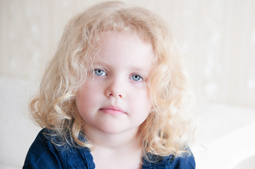 portrait of a pretty toddler with blonde curly hair