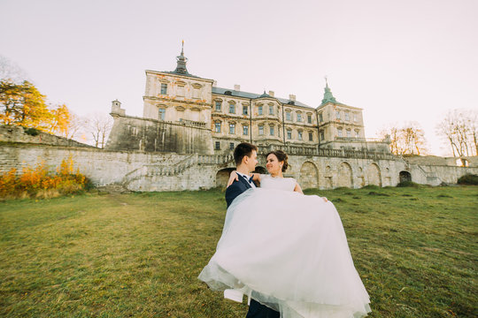 Beautiful young bride and handsome groom dancing outdoors near old mansion at sunset