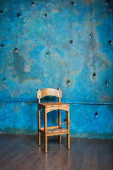 Old wooden chair in grunge room with blue wall
