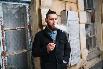 Man with  beard smoking electronic cigarette outdoor