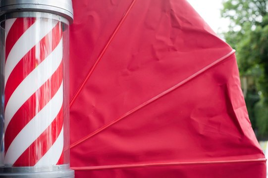 Side view of barbers pole and red awning