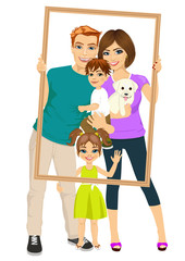 Smiling family with son, daughter and dog looking through an empty frame