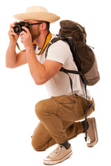 Traveler with straw hat, white shirt, backpack and photo camera
