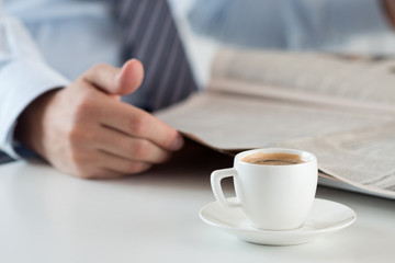 Morning espresso cup with busiessman reading newspaper on backgr