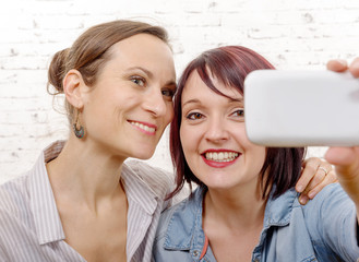 portrait of two beautiful girls making selfies at home